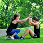 two girls giving each other high five while doing sit-ups